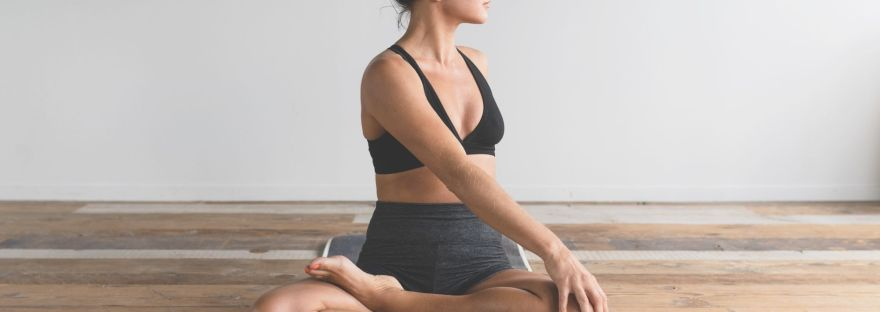 woman sitting on floor stretching and feeling clam
