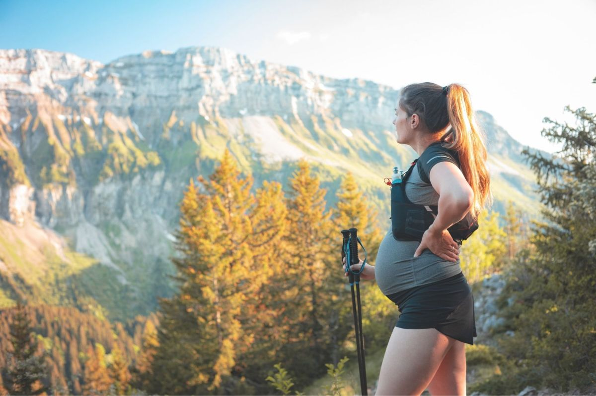 fit, pregnant woman outside hiking