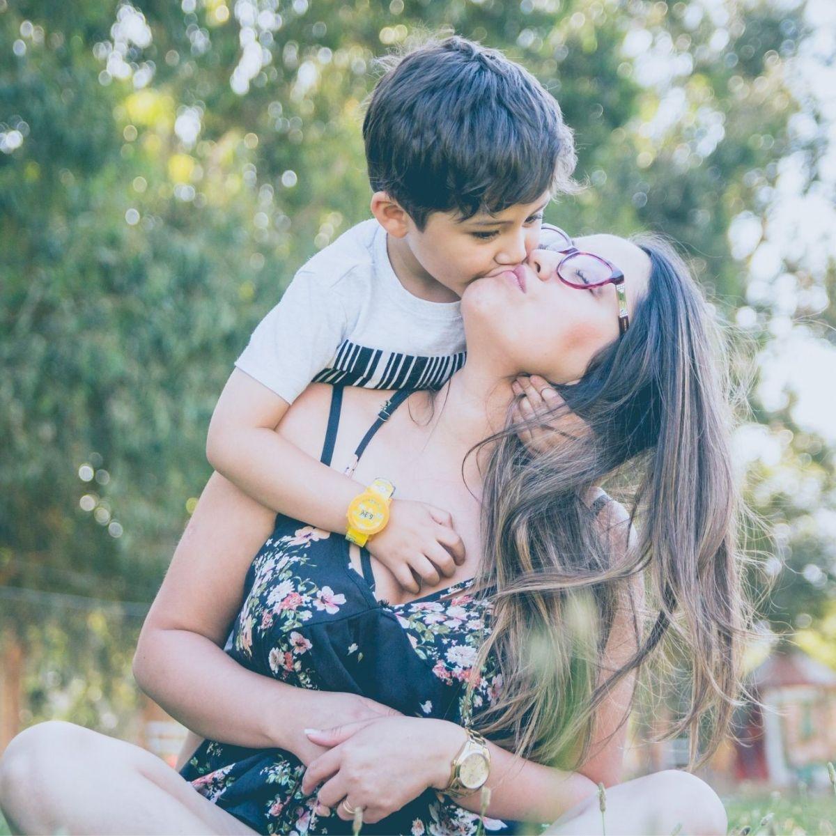 happy mom kissing her hild outside together